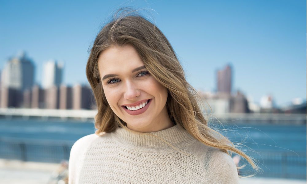 smiling woman with a city and sea in the background