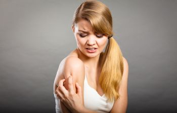 Woman suffering from chronic pain and grabbing her shoulder due to outburst of pain