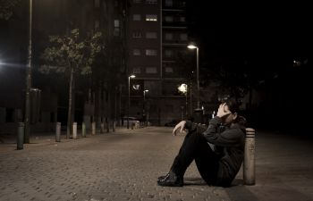 Depressed person sitting with their head in hands on the sidewalk at night